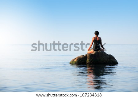 Svelte adult woman doing yoga on big stone in the sea - stock photo