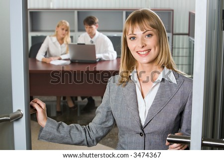 Svelte young woman in gray business suit is touching the doors and two young businesspeople on the background working on the laptop at the table