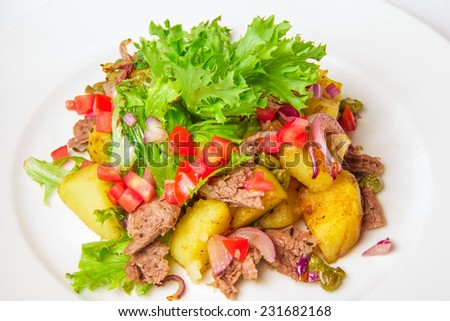 Swabian potato salad Swabian potato salad with bacon, red onion, capers in a mustard dressing on white plate - stock photo