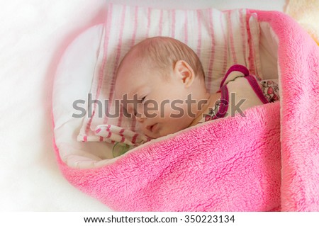 Swaddled adorable newborn girl is sleeping in bed. - stock photo
