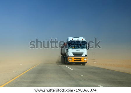SWAKOMPUND, NAMIBIA - OCTOBER 31 2013: In a year of drought goods vehicle drives through a sand storm through the Namib desert at Swakompmund, Namibia, Africa - stock photo