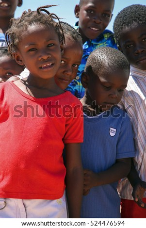 SWAKOPMUND, NAMIBIA, DEC 16: Group of Black African children posing in front of the camera in Swakopmund, a coastal city with sandy beaches facing the Atlantic Ocean. Namibia 2006