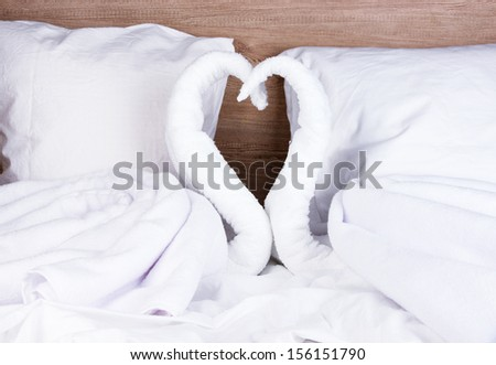 Swans made from towels on bed on wooden background