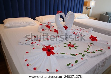 Swans Made from Towels Surround by Red Petals. Honeymoon bed decorated with red petals and towels. Romantic Flower Petal Arrangement on a Hotel Bed.  - stock photo