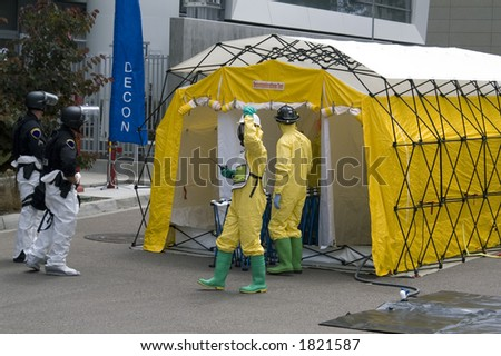 SWAT members and a Haz-Mat crew outside a decontamination shower. - stock photo