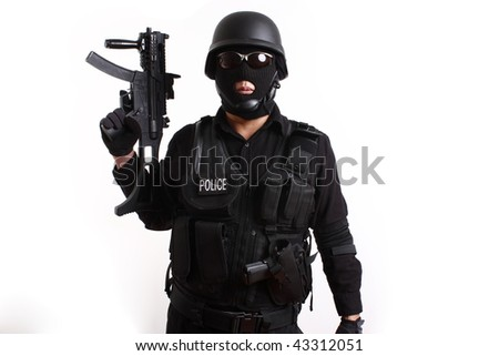 SWAT police officer holding assault gun safely with his finger away from the trigger.