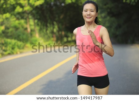 sweating healthy lifestyle fit woman runner running at forest driveway