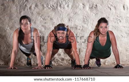 Sweating women doing push ups during bootcamp workout - stock photo