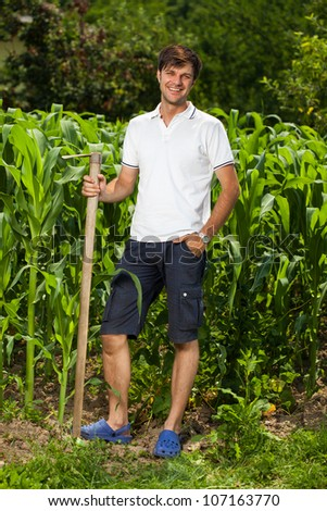 Sweating working young farmer with a hoe near a corn field