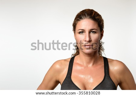 Sweaty attractive athletic fit young woman with a sheen of perspiration on her skin and lovely curly hair looking at the camera with a serious expression after a workout, head and shoulders on grey - stock photo
