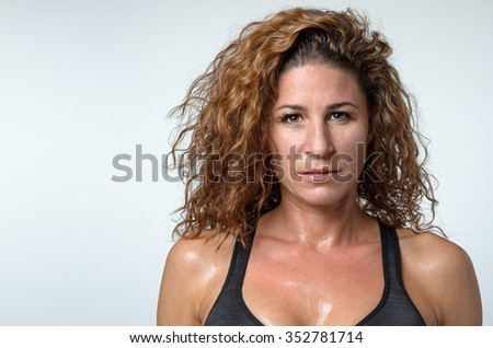 Sweaty attractive young woman with a sheen of perspiration on her skin and lovely curly hair looking directly at the camera with a serious expression, head and shoulders on grey - stock photo