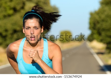 Sweaty female athlete running on rural road. Hispanic woman training sprint and exercising hard for intense marathon. - stock photo