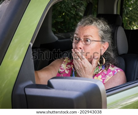 Sweaty, hot, senior woman driver looking terrified holding hand to mouth in driver's seat. - stock photo