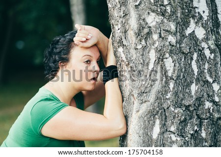 Sweaty overweight woman catching her breath after long run - stock photo