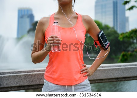 Sweaty woman drinking water during outdoor fitness workout rest. Female runner taking a running break. - stock photo