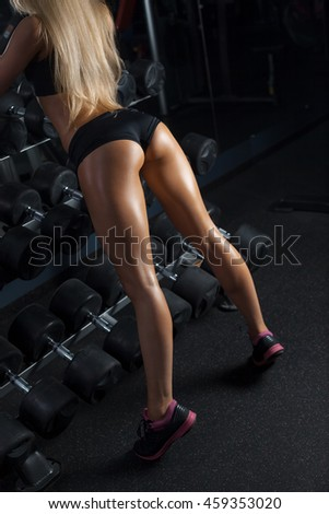 Sweaty woman having a break in a gym showing her well trained body, buttocks. Mesomorph Body Type. Girl's silhouette photo