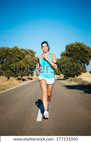 Sweaty woman running on rural road. Hispanic female athlete training and exercising hard for intense marathon. - stock photo