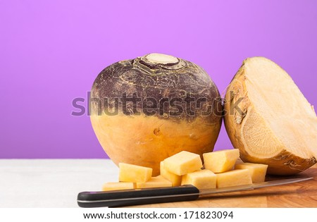 Swede on chopping board with copy space. Purple background. - stock photo