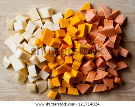 Swede, squash and sweet potato on a wooden cutting board - stock photo