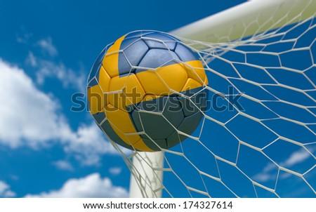 Sweden flag and soccer ball, football in goal net - stock photo