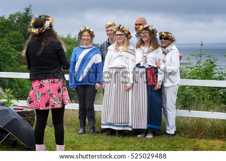 SWEDEN,June 19, 2015:Group portrait of an unidentified family celebrating the Midsummer holiday, wearing traditional costumes and floral head wreaths. Location: Uto Island in the Swedish Archipelago.