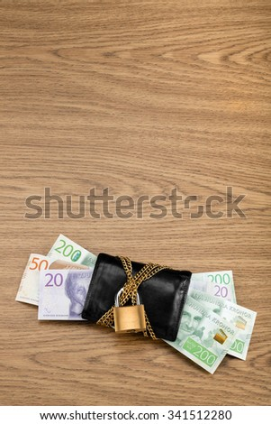 Swedish banknotes in a black wallet locked with a golden chain and padlock on wooden table with copy space above. These are some of the new banknotes that were introduced in Sweden year 2015. - stock photo