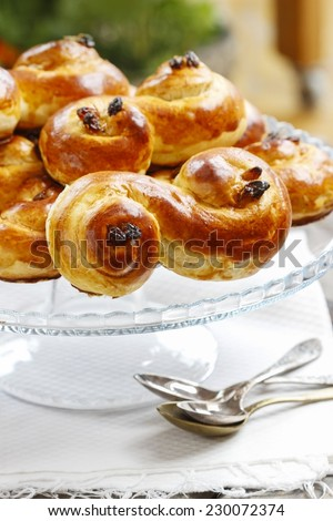Swedish christmas. Traditional swedish buns on cake stand in christmas setting. A saffron bun, in Swedish lussebulle or lussekatt. - stock photo