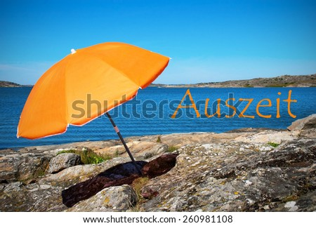 Swedish Coastline Bohuslan Archipelago Swedish West Coast With Rocks And Cliffs And Beach With Orange Parasol And German Text Auszeit Means Downtime With Ocean And Open Sea Sunny Weather With Blue Sky - stock photo