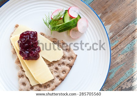 Swedish crisp bread topped with cheese and lingonberry jam and served with a side salad of cucumber, dill and radishes. - stock photo