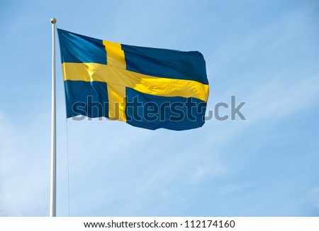 Swedish flag waving in the blue sky on a sunny day. - stock photo
