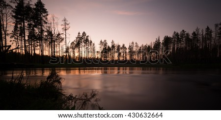 Swedish river photographed with long exposure at sunset, reflections in the water