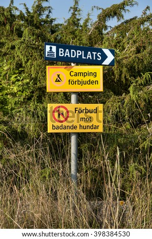 Swedish signs which indicate the direction to a base plate, that camping is not allowed and dogs are not allowed to have a swim