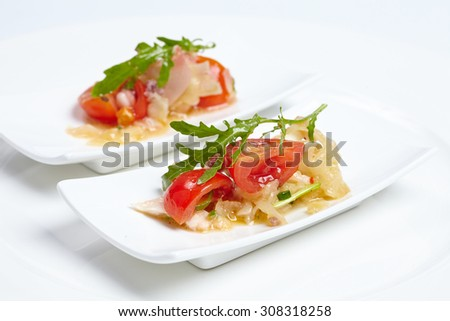 Swedish table appetizers: tomatoes, cheese, arugula, octopus, onion fennel