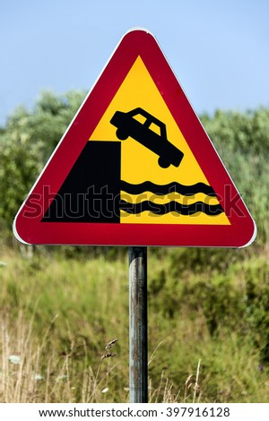 Swedish traffic sign with car falling from a pier - Watch out, dangerous edge. - stock photo