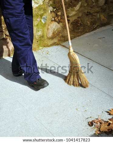 Sweeper, municipal cleaning worker sweeping the autumn leaves