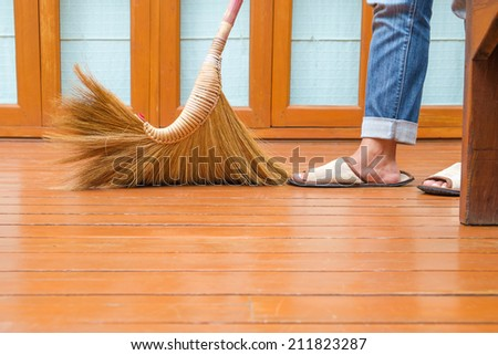 Sweeping dust on wood floor, closeup  at broomstick with woman's feet in slippers