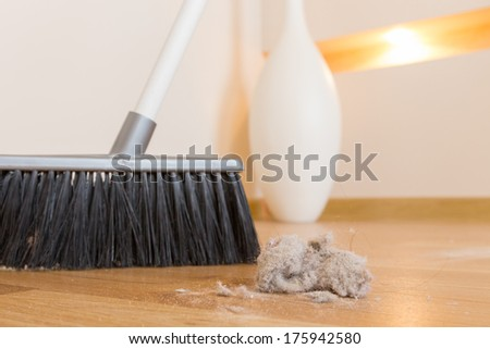 Sweeping dust with black broom on a wooden floor - stock photo