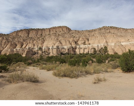 Sweeping landscape horizontal view on partly cloudy day of Tent Rocks National Monument on Cochiti Pueblo in Sandoval County New Mexico, USA - stock photo