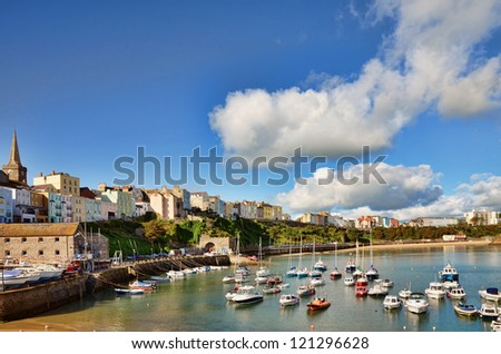 Sweeping view of Tenby harbour with boats, on a summers day with a vivid blue sky and cumulus clouds.