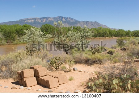 Sweeping view of the Sandia Mountains in early summer with Rio Grande river in the foreground - stock photo