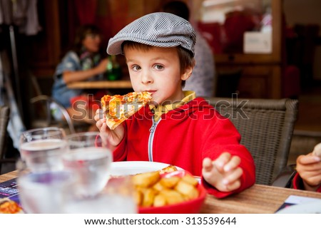 Sweet adorable child, boy, eating pizza at a restaurant, , summertime - stock photo