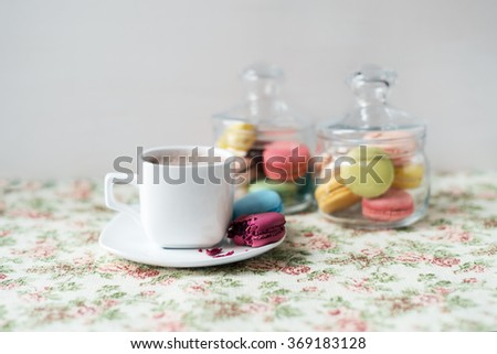 Sweet and beautiful French macaroon stored in glass jars. Tasty dessert with a cup of coffee. - stock photo