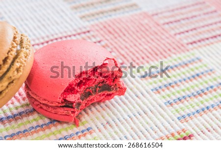 Sweet and colorful french macaroons on cotton cloth background .