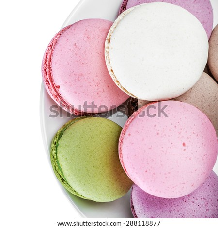 Sweet and colourful french macaroons on white background. focus on a plate with macaroon