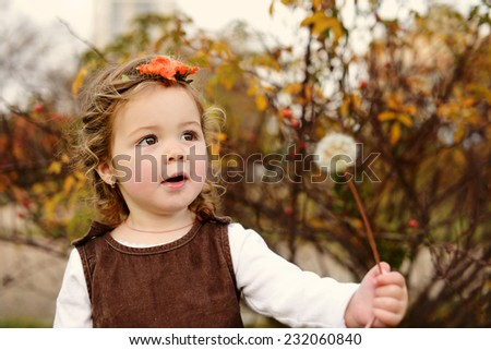 sweet and fashion toddler girl in fall with dandelion - stock photo