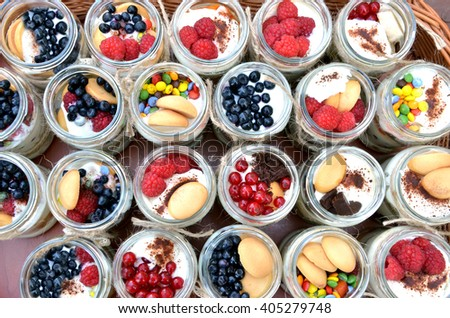 Sweet and healthy dessert: many glasses filled with cream and tiny colorful fruit - stock photo