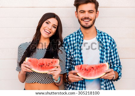 Sweet and juicy like their love. Cheerful young loving couple holding slices of watermelon and looking at camera while standing outdoors togehter - stock photo