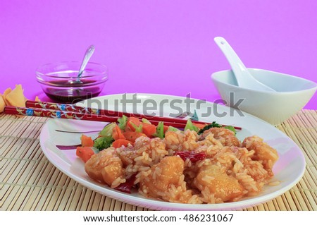 Sweet and Sour Chicken Dinner on bamboo place mat against pale purple background.