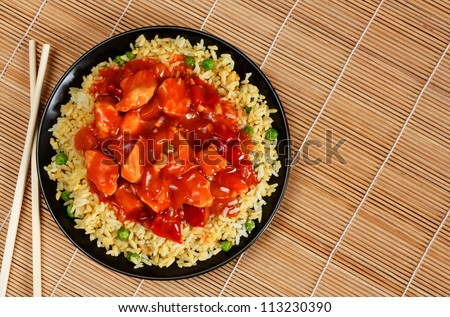 sweet and sour chicken with fried rice - popular oriental cuisine - stock photo