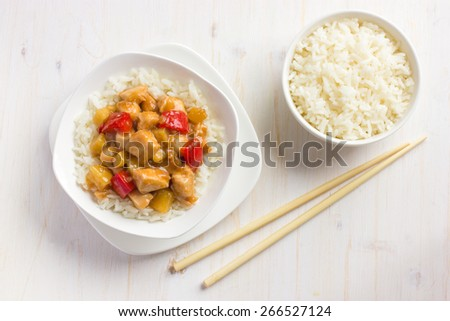 Sweet and sour chicken with rice in white bowl, top view